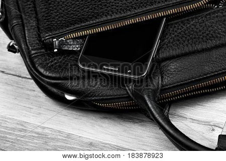 Smartphone in businessman bag closeup.Copy space cellphone concept advertising