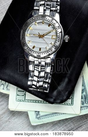 Watch on black leather wallet with money..Wooden background.Busynesman set
