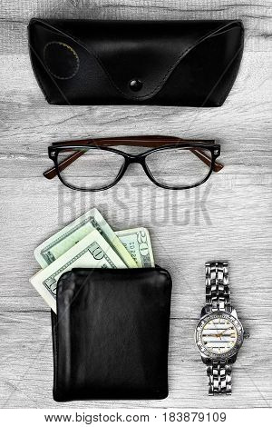 Men accessories .Eyeglasses with leatehr case.Black leather wallet with money. Watch .Wooden background.Bussynesman set