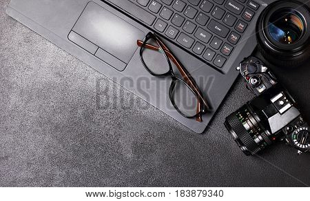 Office desk table with laptop, photo camera, lenses, glasses and flash drives. Top view with copy space.