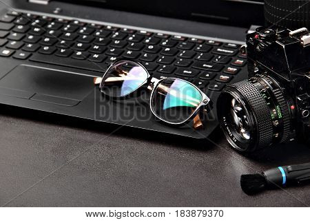Office desk table with laptop, photo camera, lenses, glasses and flash drives.Copy space.Tools of photgrapher