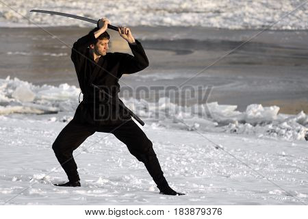 Ninja in black kimono with sword is practicing martial arts in the snow at winter.