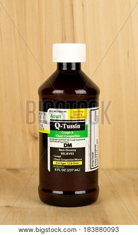 RIVER FALLS,WISCONSIN-APRIL 28,2017: A bottle of Qtussin brand cough suppressant with a wood background.