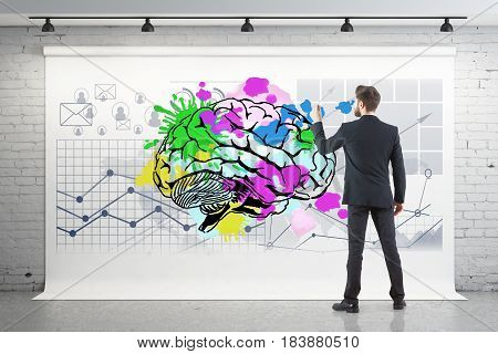 Back view of young businessman drawing colorful brain and business charts on poster hanging in brick interior. Brainstorming concept. 3D Rendering