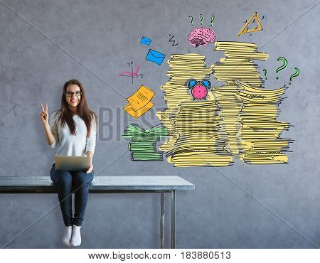 Cheerful young european girl sitting on table and showing peace sign on concrete background with paperwork piles. Workload concept