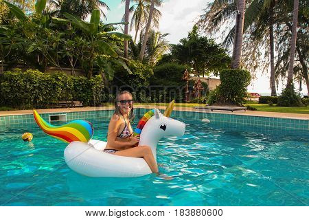 Young Caucasian Woman in Bikini Relaxing on Floating Unicorn