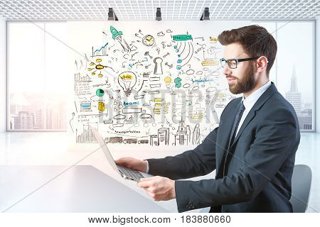 Side view of young businessman using laptop in modern office with desktop and panoramic city view. Computing concept. 3D Rendering