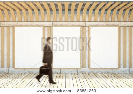 Blurry walking businessman in interior with three blank posters. Museum concept. Mock up 3D Rendering