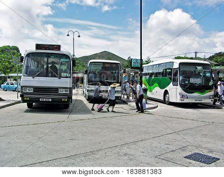 Ngong Ping, Hong Kong - March 24, 2003: Buses and people at the Ngong Ping Bus Terminus on the island of Lantau in Hong Kong