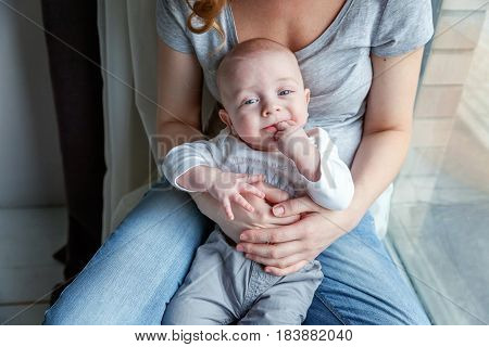 Mother holding her newborn child. Woman and new born boy relax near the windiow. Mother breast feeding baby. Family at home. Young mother playing whith her newborn son
