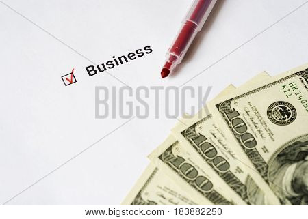 business questionnaire. Red pen, dollars and inscription with check mark on the white paper