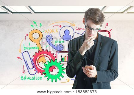 Handsome young businessman using smartphone in interior with colorful sketch on wall. Communication concept. 3D Rendering