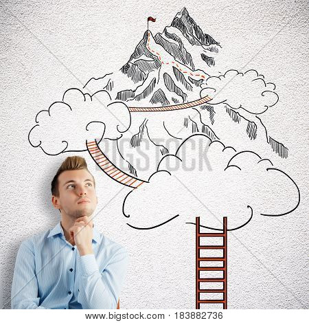 Thoughtful young man on concrete background with drawn ladder clouds and way to mountain top. Success concept