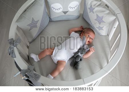 Newborn boy lies in a round bed on his back