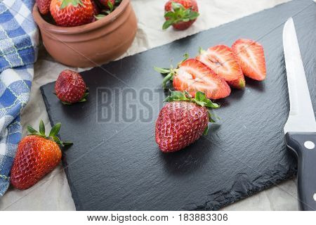 Red Ripe Strawberries  On A Table Some Sliced And A Knife.