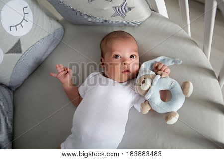 Newborn boy lies in a round bed on his back