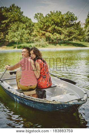 Young Beautiful Happy Loving Couple Rowing A Small Boat On A Lake. A Fun Date In Nature. Couple In A