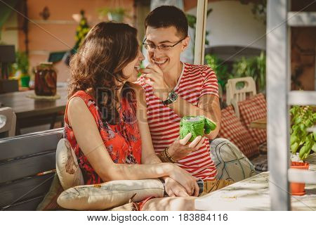 Young Beautiful Happy Loving Couple Sitting At Street Open-air Cafe. Men Is Giving Sweets To His Gir