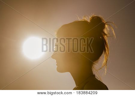 Young attractive woman on the beach at sunset drinking from glass in backlight scene