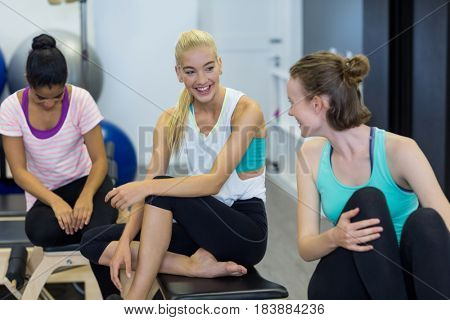 Smiling fit women interacting with each other in gym
