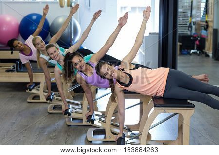 Portrait of smiling women exercising on wunda chair in gym
