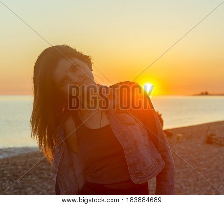 Young attractive woman on the beach at sunset time in backlight scene