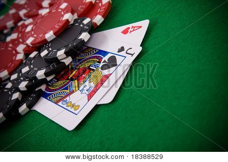 Ace of hearts and black jack with black and red poker chips in the background.