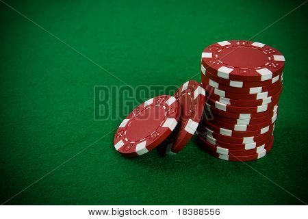 Stack of red poker chips on a green poker table background.