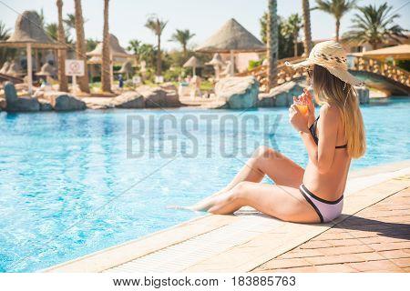 Beautiful Woman In Bikini And Sunlasses Sitting In Swimming Pool With Cocktail.