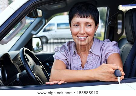 Portrait of attractive senior smiling woman holding the keys from new car