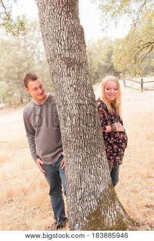 Pregnant Wife With Husband Standing behind Tree