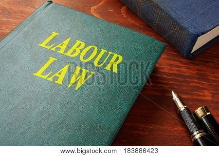Book with title labour law on a wooden surface.