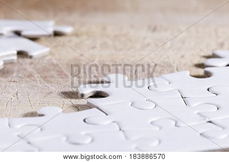 close up of a white jigsaw over a wooden table. problem solving. business. strategy.