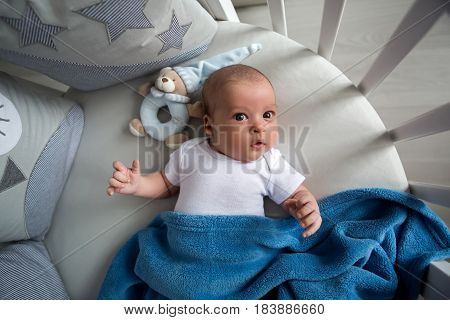 Newborn boy lies in a round bed on his back with a rattle
