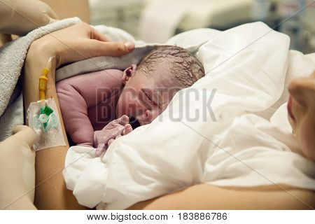 Newborn baby boy after birth is on her mother's arms