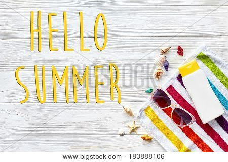 Hello Summer Text On  Colorful Towel, Sunglasses, Yellow Sunscreen And Star Shells On White Rustic W