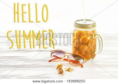 Hello Summer Text, Vacation Concept. Yellow Cocktail Juice With Apricot,  Sunglasses And Shells In L
