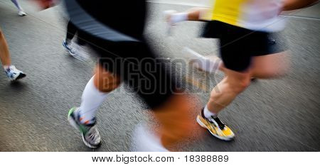 People running in city marathon - motion blur
