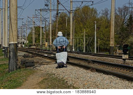 Grandma with a cart goes along the railway