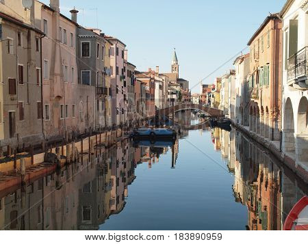 Chioggia, Italy. Old palaces reflected in the water of a canal.