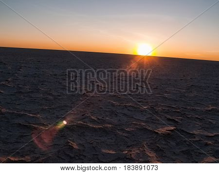 Sun on curved horizon over baked dry cracked crust of Makgadikgadi Pans National Park scenic large flat area of salt pan desert of Botswana