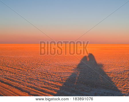 Shimmering horizon and long shadows as sun sets across Makgadikgadi Pans National Park scenic large flat area of salt pan desert of Botswana