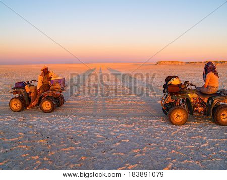 Makgadikgadi, Botswana -August 29, 2007; Tourist and guide in glow of setting sun on quad bikes stop while crossing Makgadikgadi Pans National Park scenic large flat area of salt pan desert to take in view Botswana