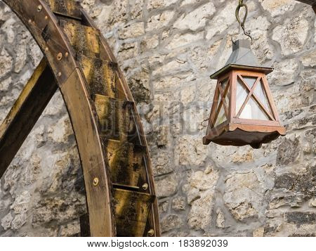 Old lantern hanging on the stone wall and water will