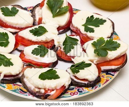 Colourful slices of cheese and tomato arranged alternately on a plate and garnished with herbs
