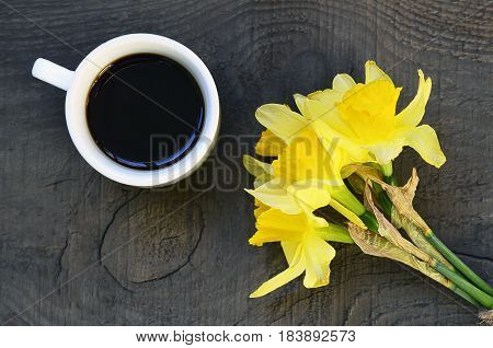 Coffee cup and bouquet of narcissus flowers on old rustic wooden table.Coffee mug and spring flowers.Spring morning,Breakfast,Good morning concept.