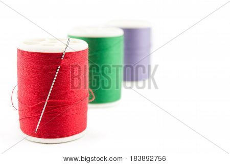 Spool Of Green Thread And Needle On White Background