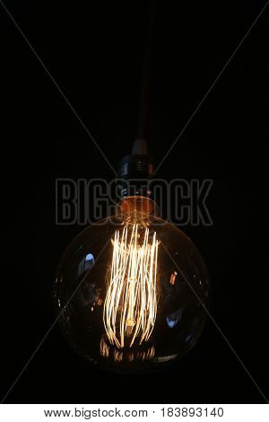 Oldstyle wolfram light bulb shining in the dark