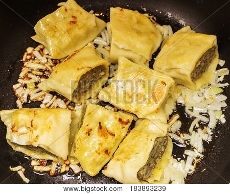 Fried Swabian ravioli so-called'Maultaschen' with meat filling served with roasted onions,