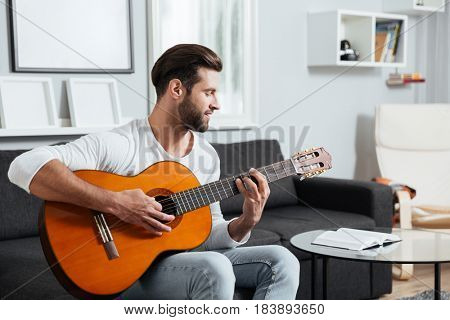 Image of young smiling man sitting on sofa indoors at home while playing on guitar. Looking aside.